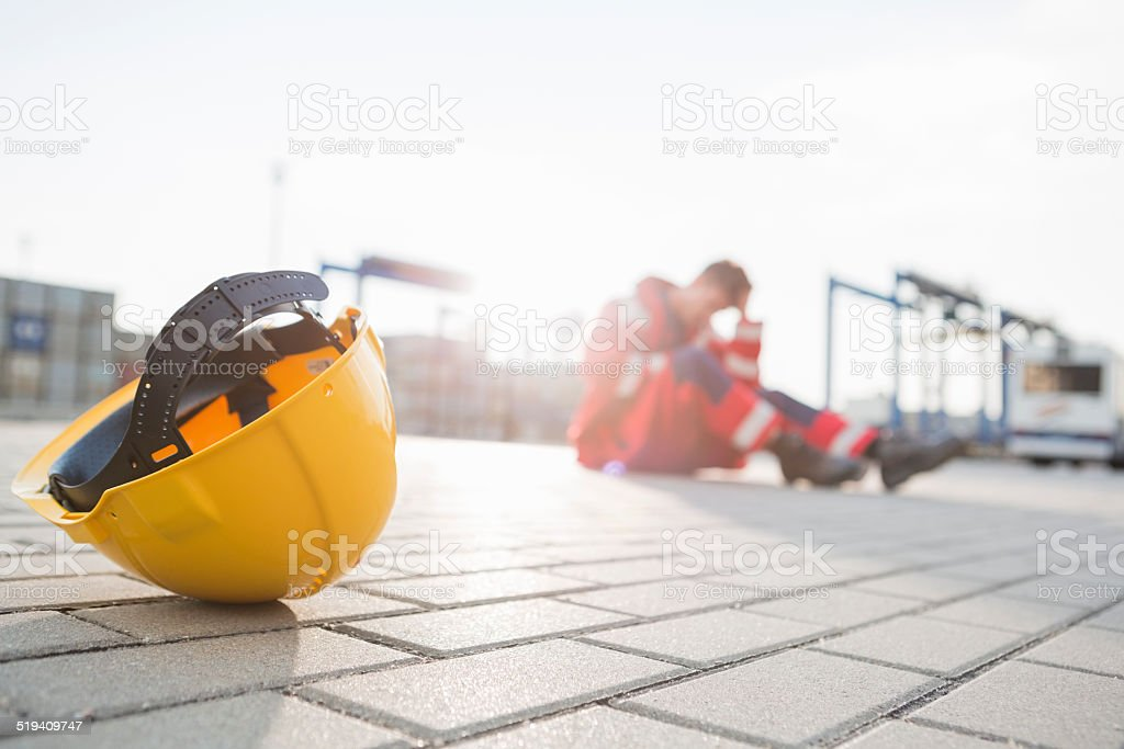 Yellow hardhat at shipyard with depressed male worker in background stock photo