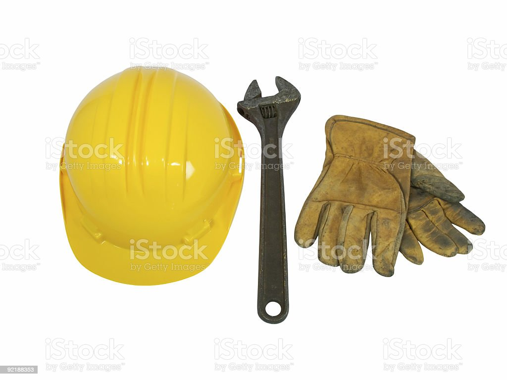 Yellow hardhat, old leather gloves and wrench royalty-free stock photo