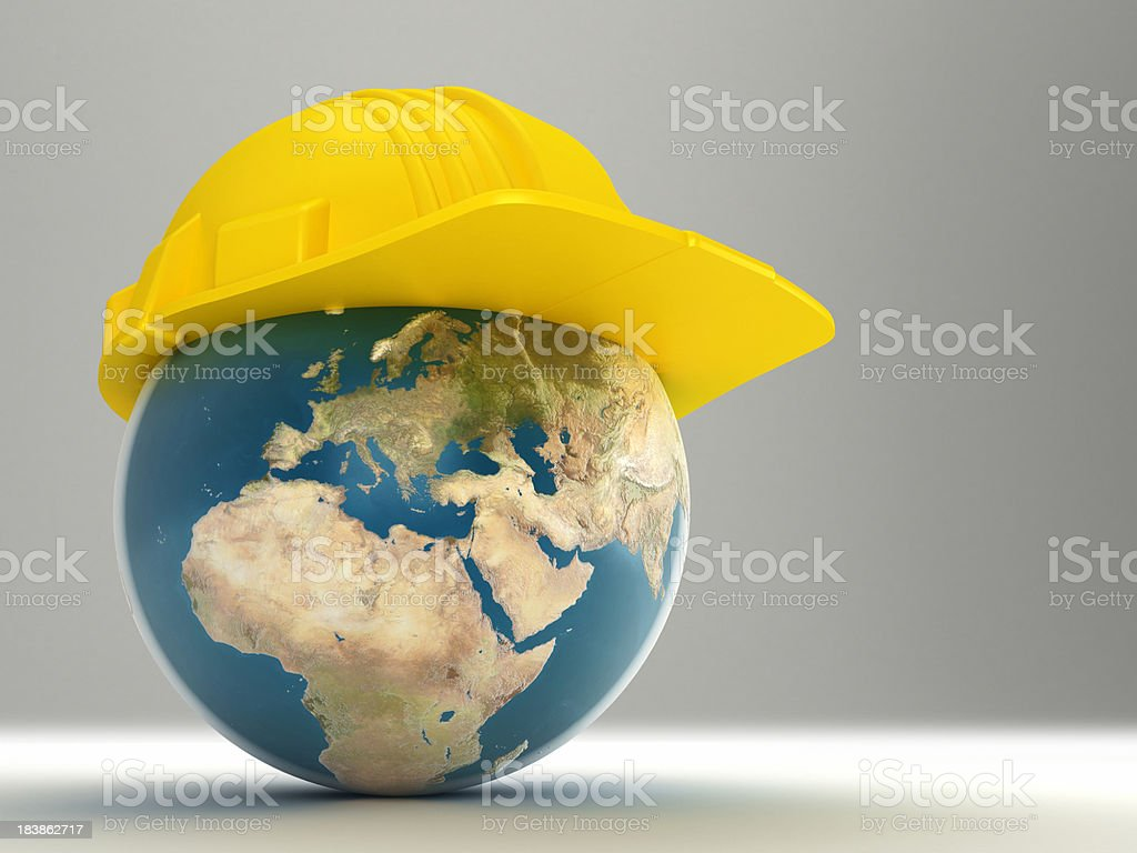 Yellow hardhat on top of digital image of Earth royalty-free stock photo