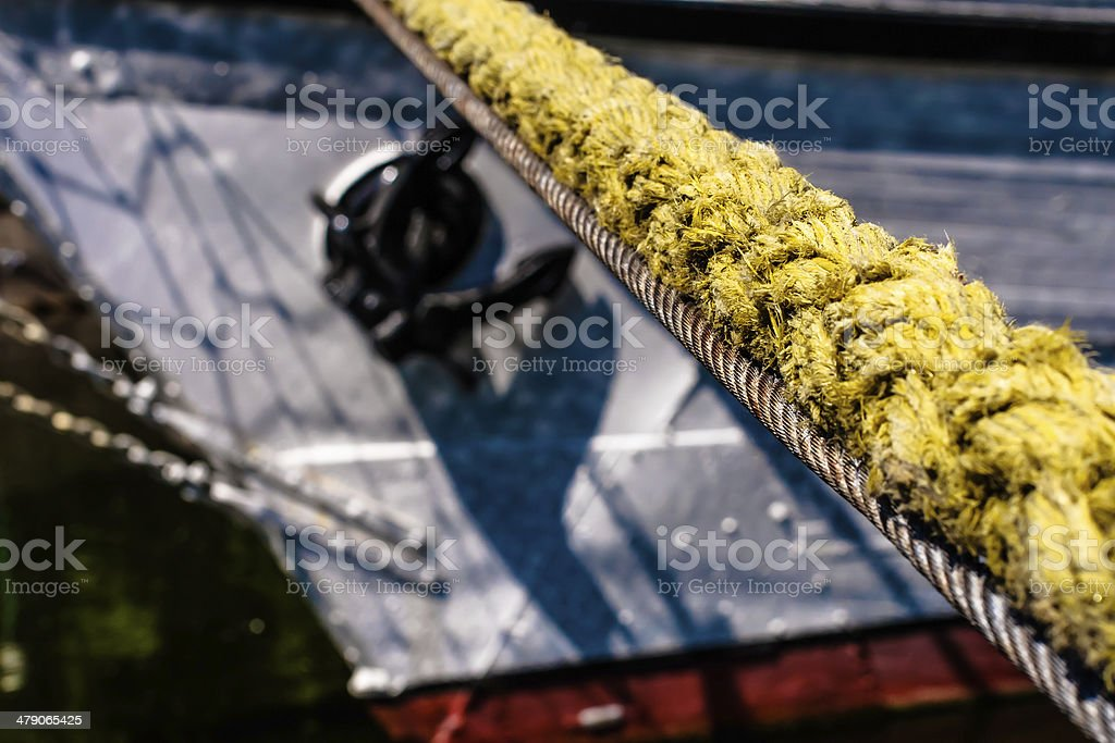 Yellow hawser, mooring line with visible fragment of the ship. stock photo