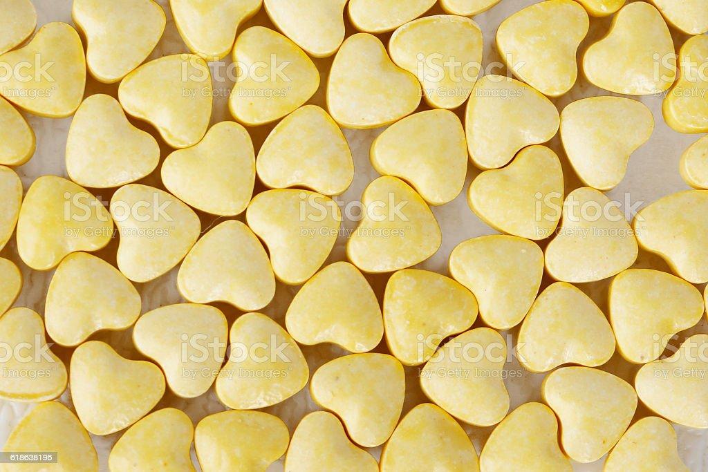 Yellow heart shaped pills stock photo