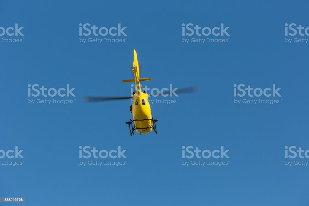 Yellow helicopter used for rescue operations, Medical rescue helicopter flying rescue injured climber on the Tre Cime. Italy, Dolomites stock photo