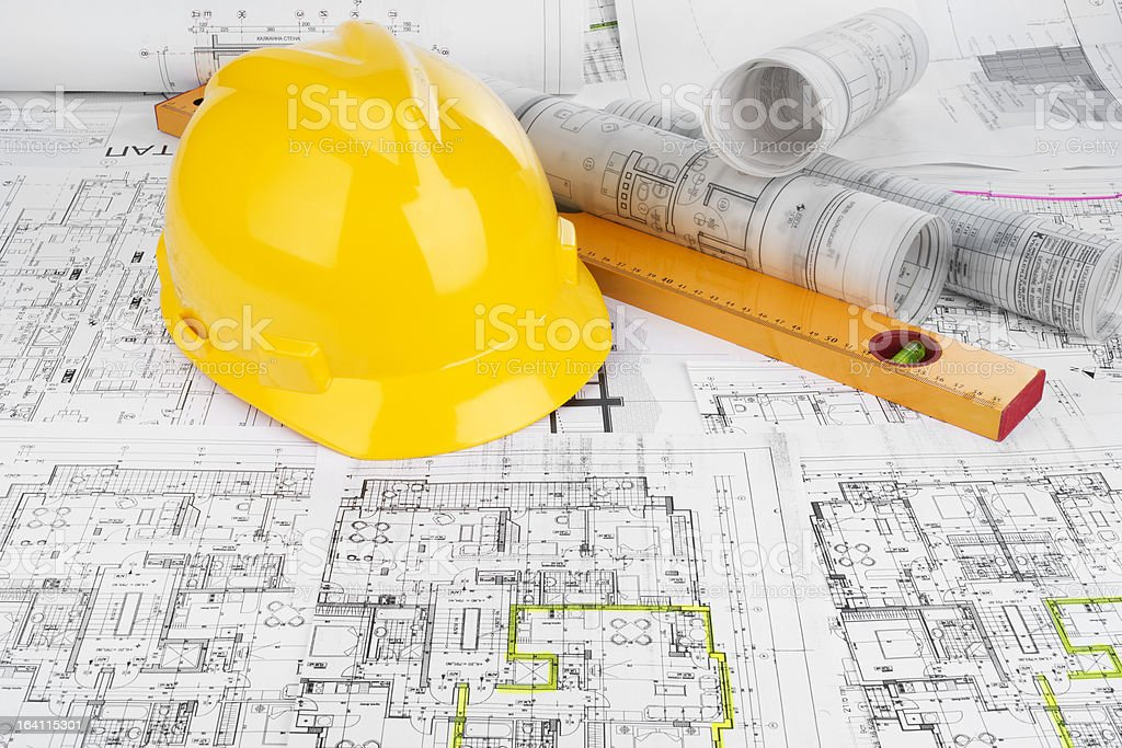 Yellow helmet, level and project drawings royalty-free stock photo