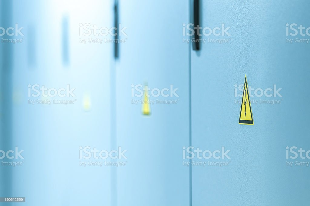 Yellow high voltage sign on blue doors. royalty-free stock photo