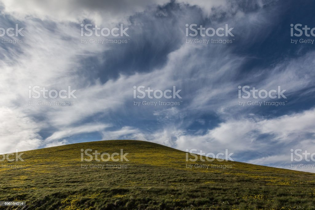 Yellow hill and sky stock photo