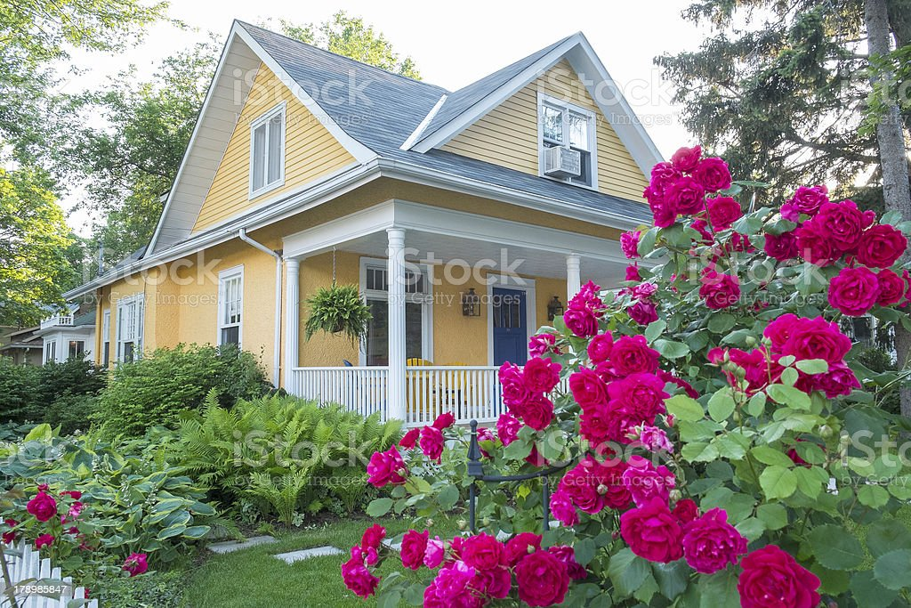 Yellow house with pink flowers stock photo
