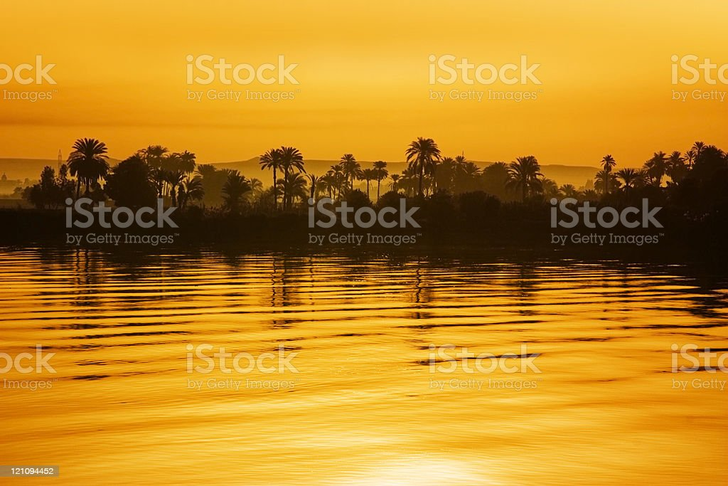 Yellow hue sunset with trees and hills along the Nile River stock photo