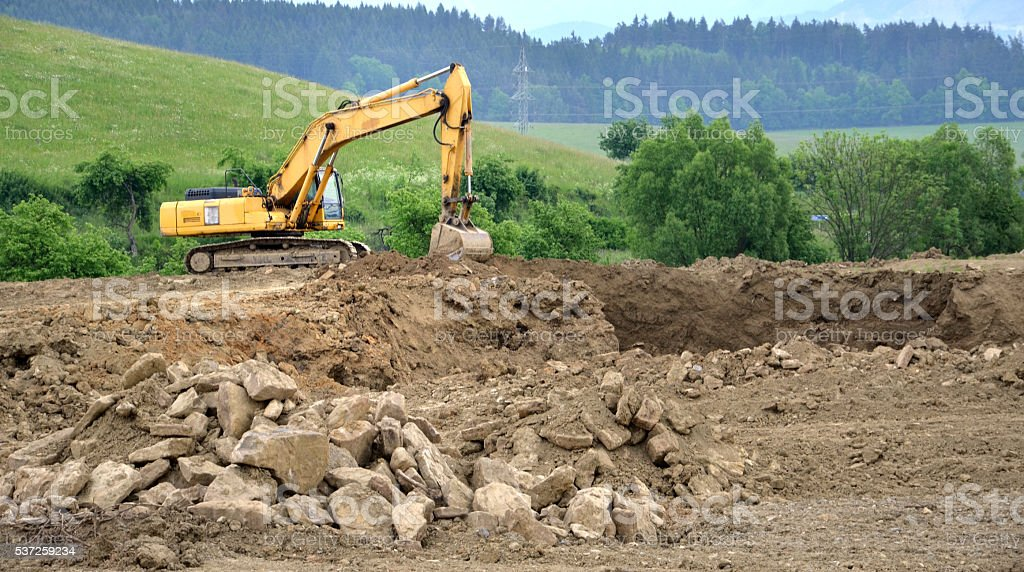 Yellow hydraulic excavator in working process on mass of ground