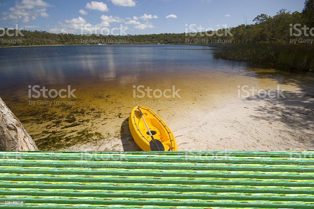 Yellow kayak on the beach of a still lake stock photo