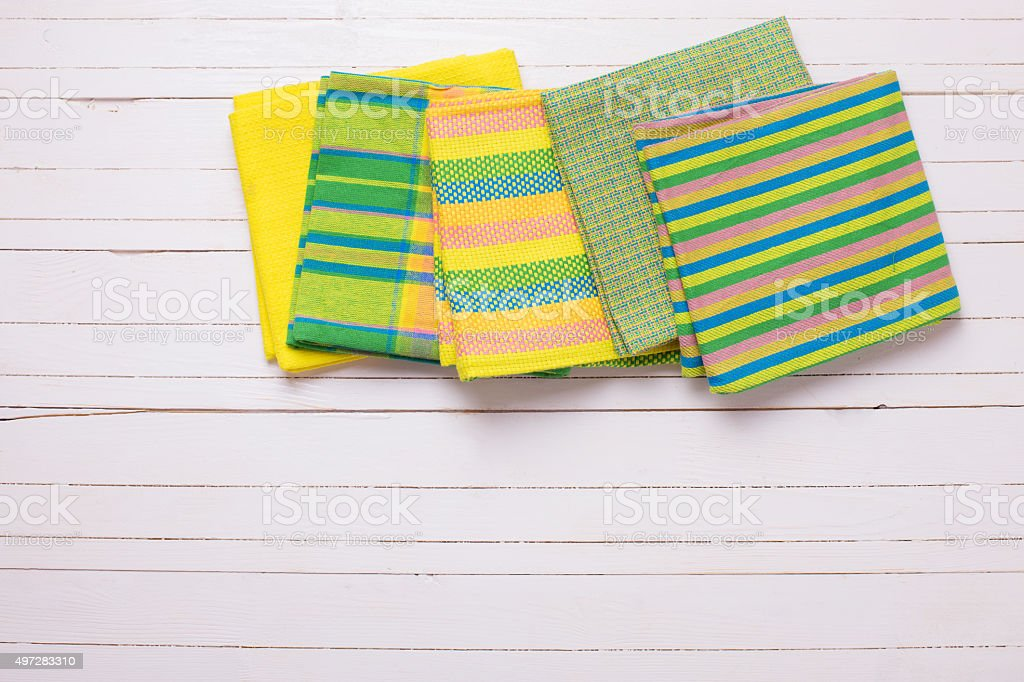 Yellow  kitchen towels  on white wooden background. stock photo