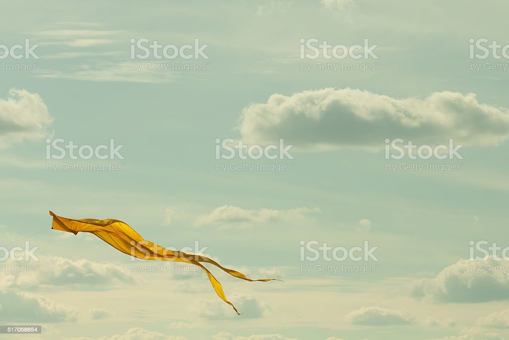 Yellow kite flying in the cloudy sky. Summer landscape concept stock photo