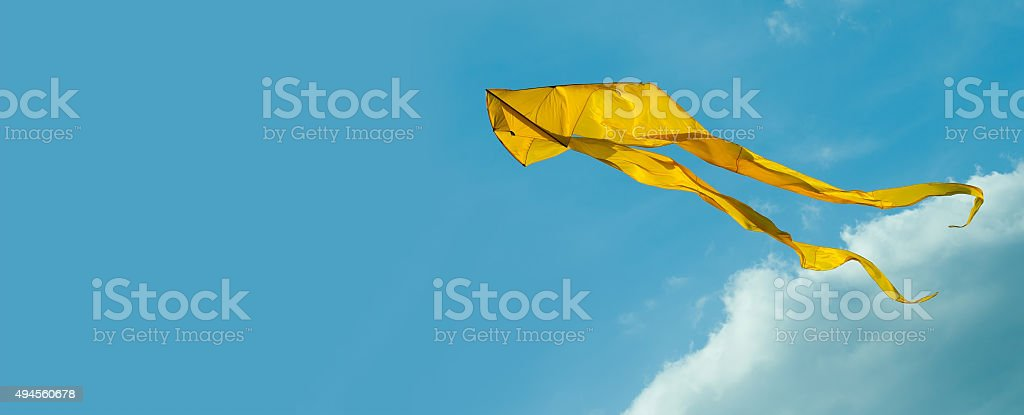 Yellow kite flying in the sky. Cloudy day. Blue background stock photo