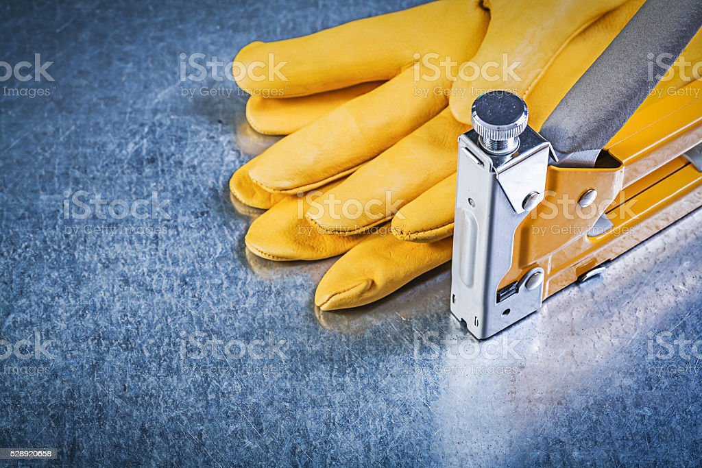 Yellow leather protective gloves construction stapler on metalli stock photo