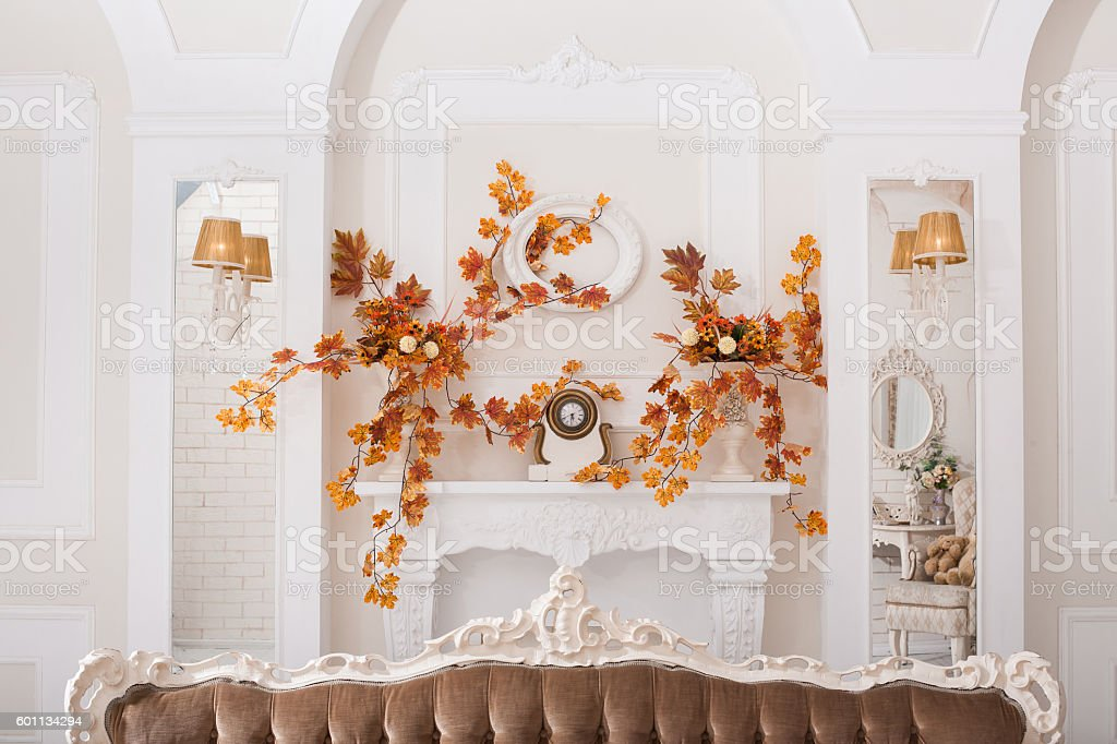 Yellow leaves entwined wall of white hall with fireplace stock photo