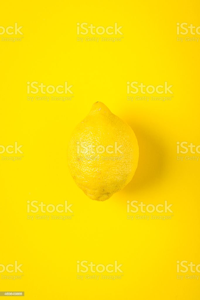 Yellow lemon on yellow paper background, minimalist still life stock photo