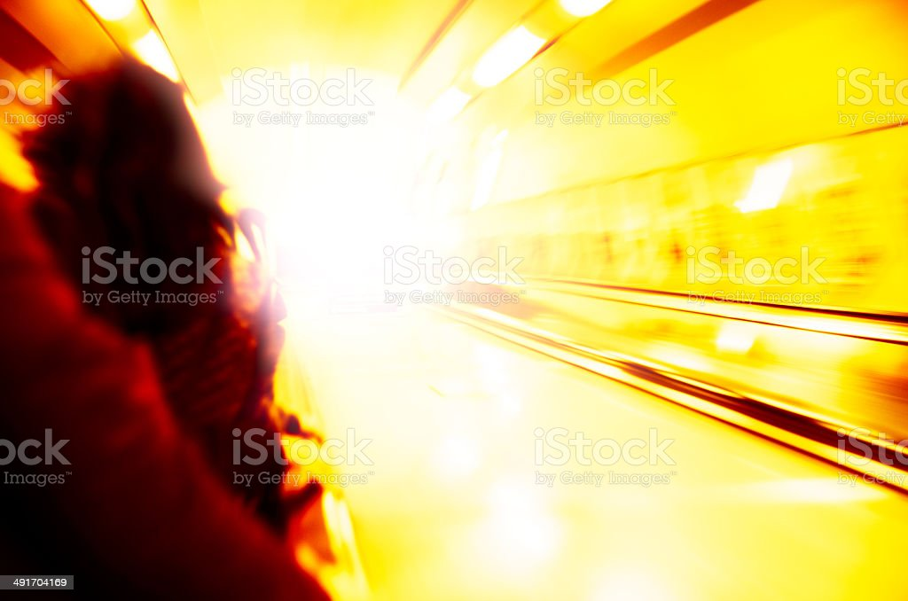 Yellow light at the end of escalator stock photo