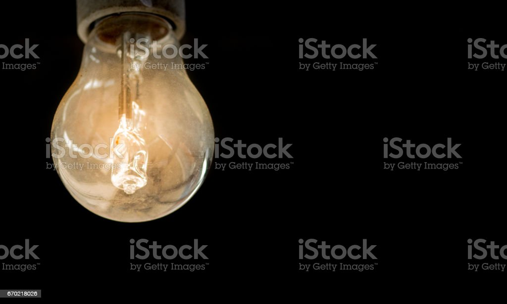 Yellow light bulb over black background isolated - idea, thinking, power and creativity concept stock photo