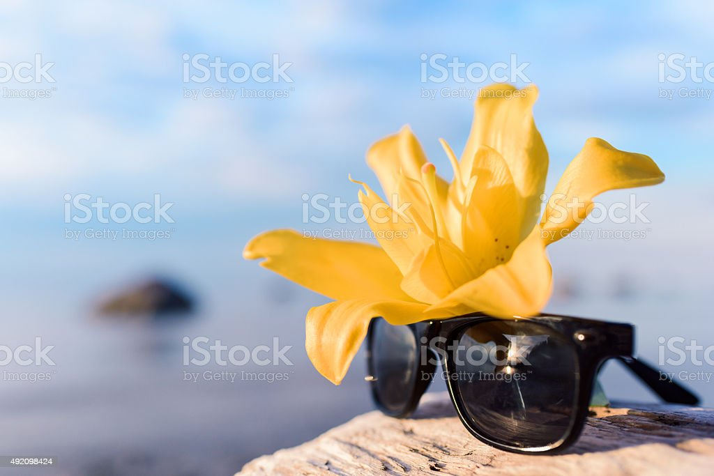 Yellow lily and glasses stock photo