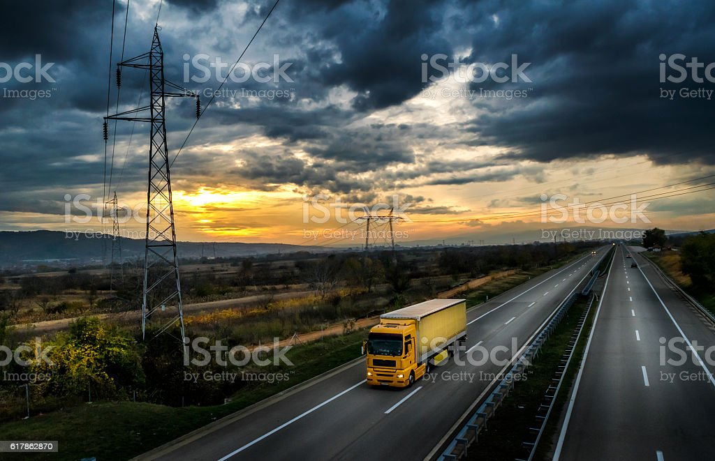 Yellow lorry on a highway at sunset stock photo