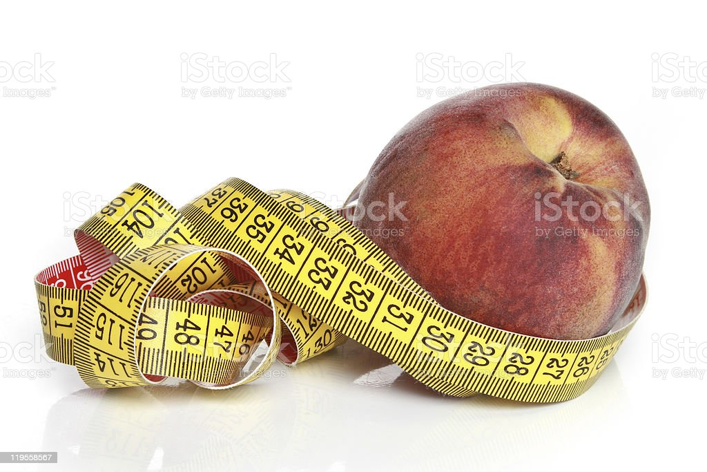 Yellow measuring tape and peach royalty-free stock photo