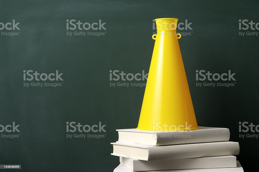 Yellow megaphone on stacked blank books in front of blackboard stock photo