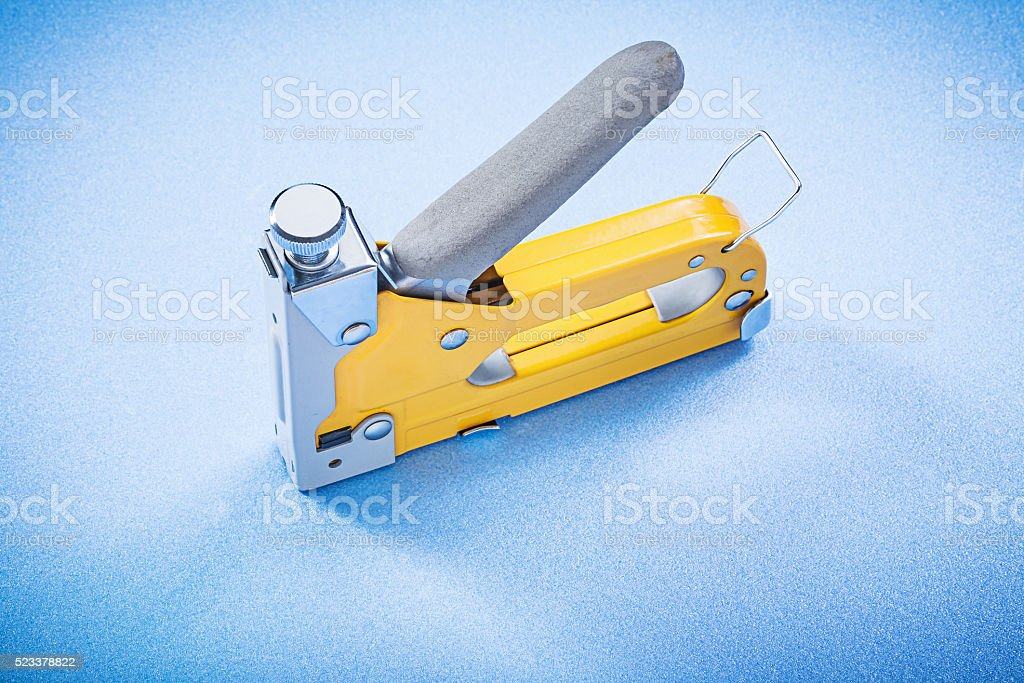Yellow metal construction stapler on blue background top view stock photo