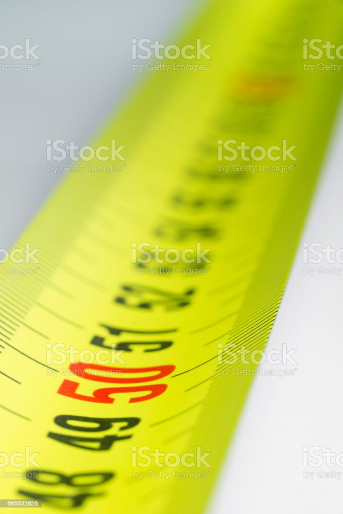 Yellow metal industrial tape measure with standardized metric system stock photo