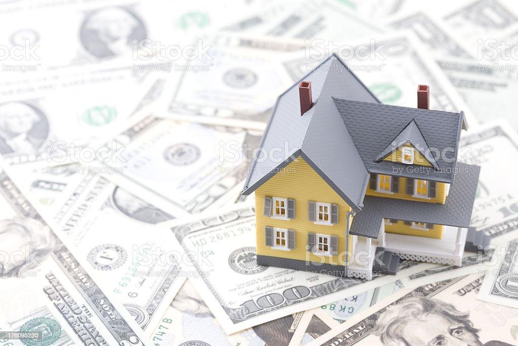 Yellow Miniature House on top of U.S. Money stock photo