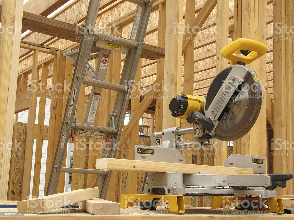 Yellow Miter Saw and Lumber Against Framed Construction Background royalty-free stock photo