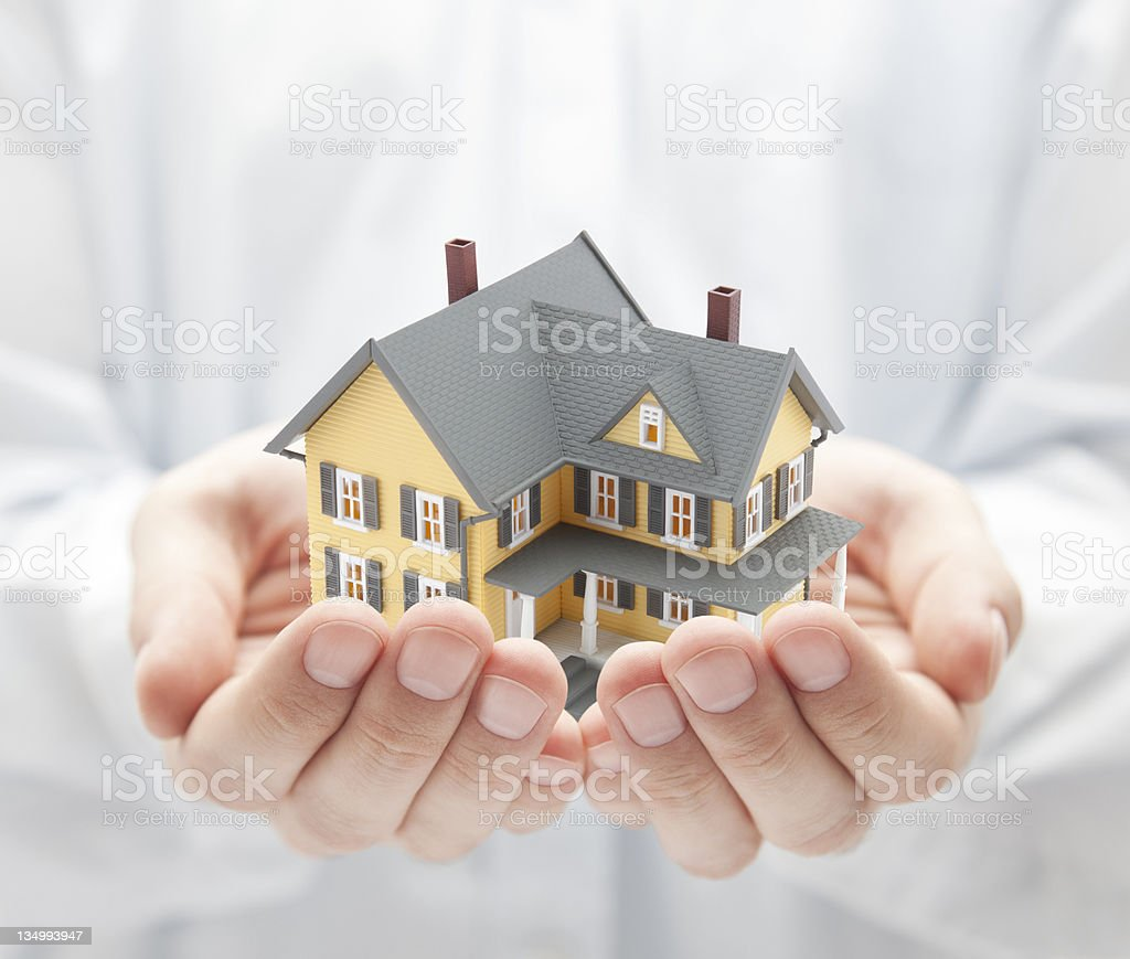 Yellow model house in two cupped hands stock photo