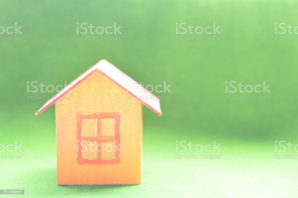 yellow model of house as symbol on green background stock photo