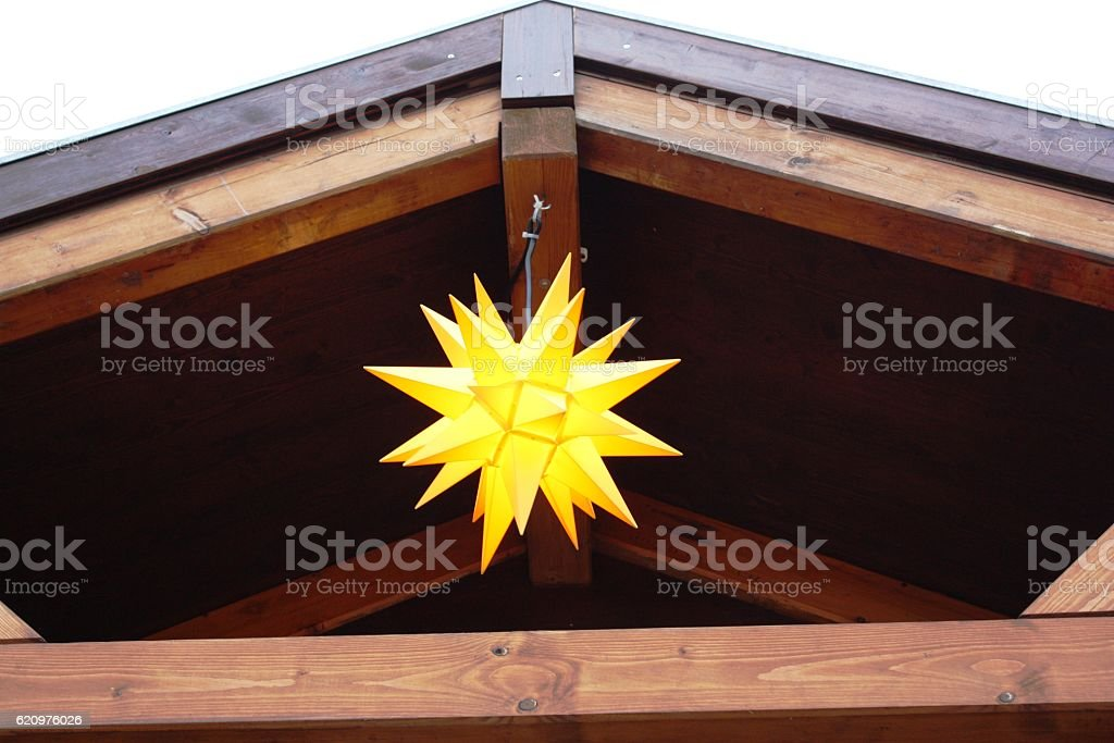 Yellow Moravian star under the roof at Christmas stock photo