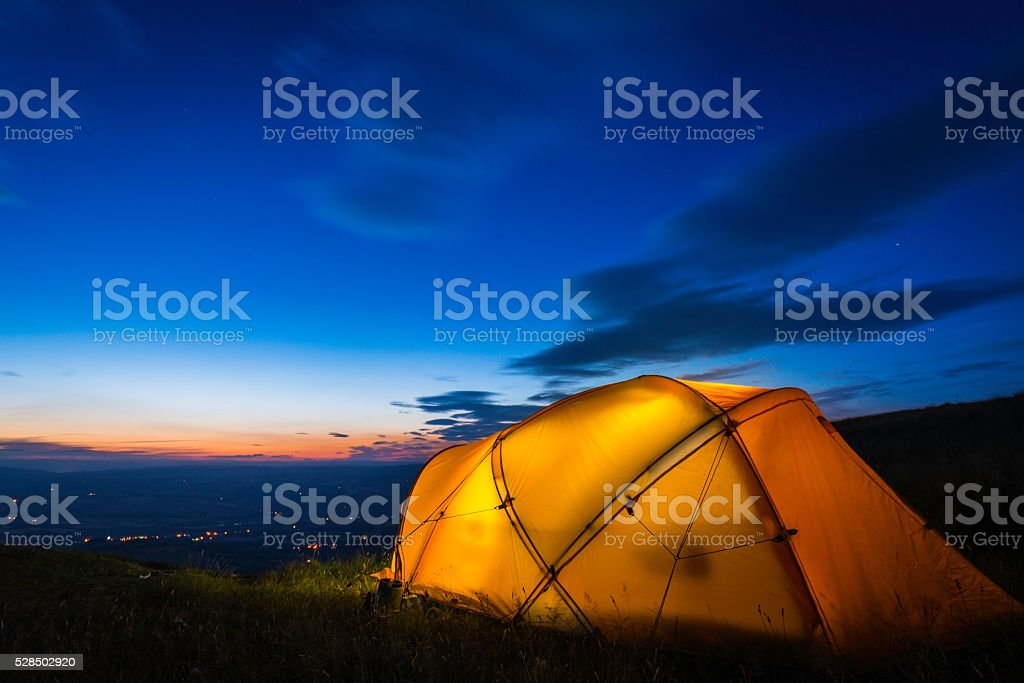 Yellow mountain tent illuminated at dusk on summer mountain ridge stock photo