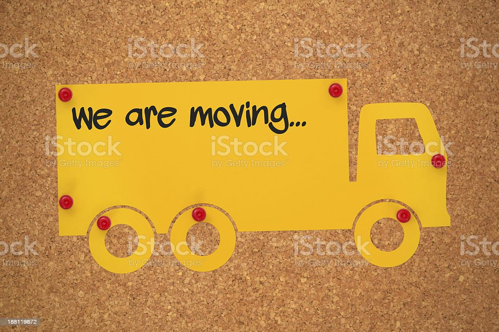 Yellow moving van cutout tacked to a cork board stock photo