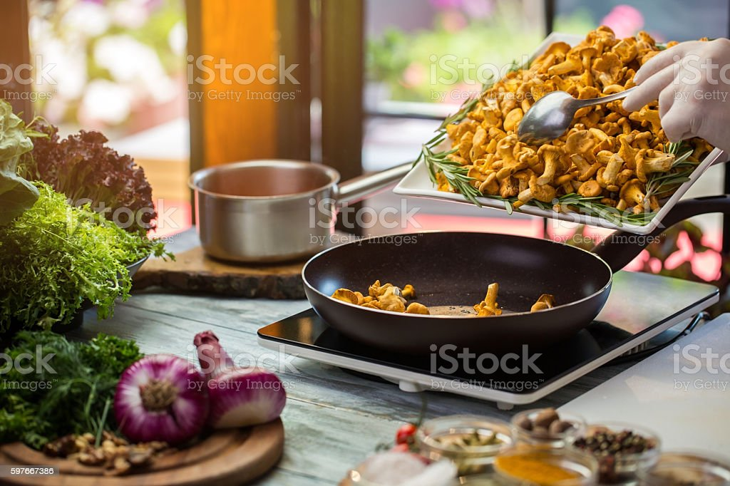 Yellow mushrooms on black pan. stock photo