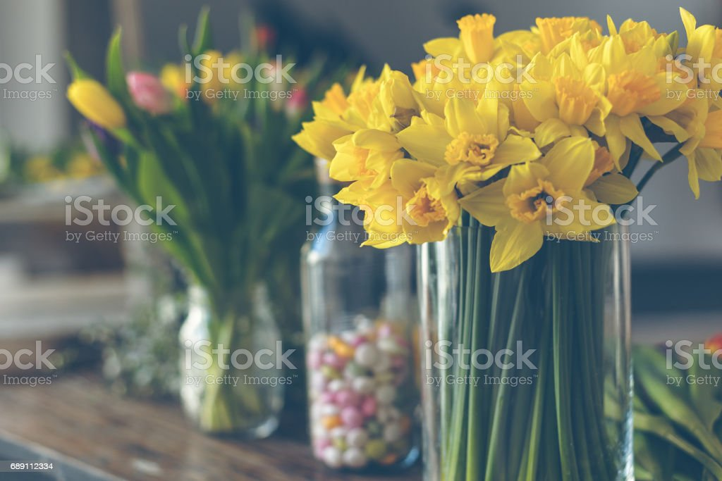 Yellow narcissuses bouquet in a glass vase stock photo