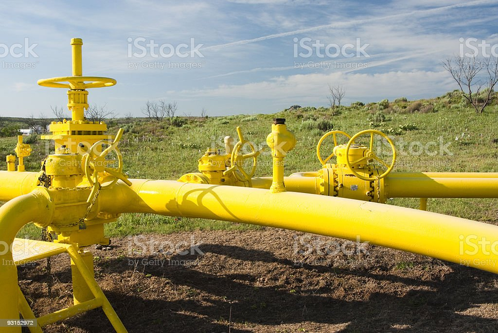 Yellow natural gas pipeline in a field on a sunny day stock photo