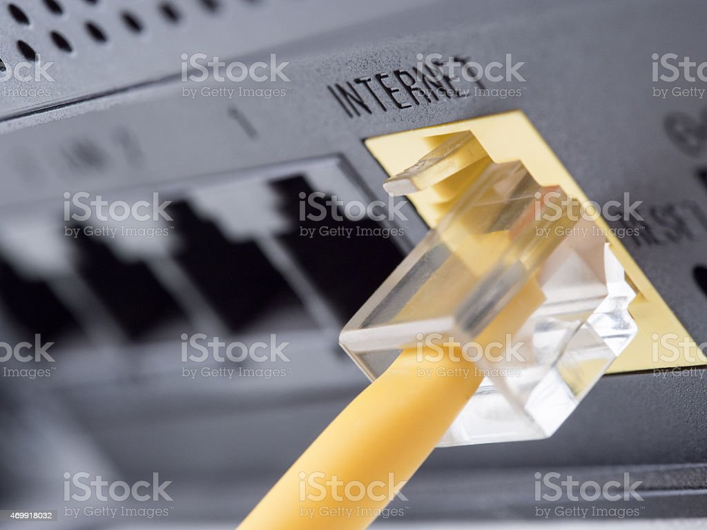 Yellow network cable connecting to the internet slot stock photo