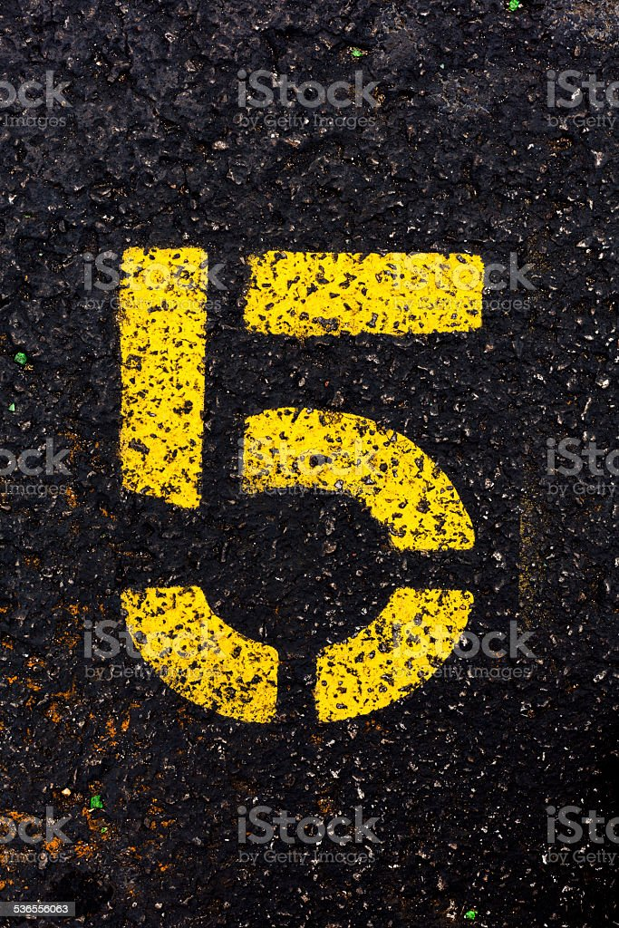 Yellow Number Five on Asphalt stock photo
