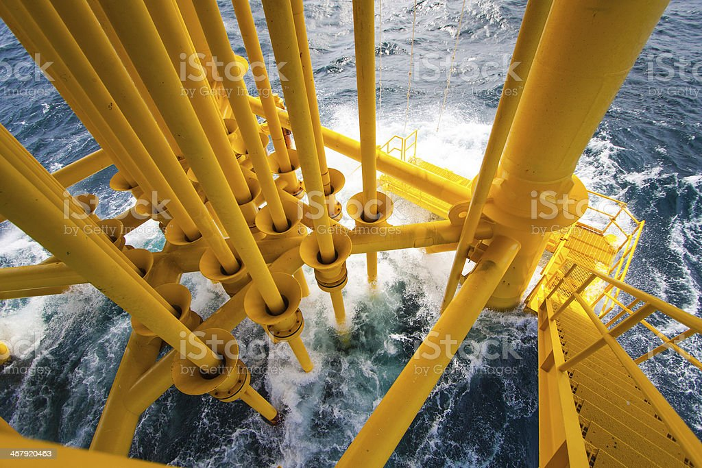 Yellow oil and gas producing slots at an offshore platform stock photo