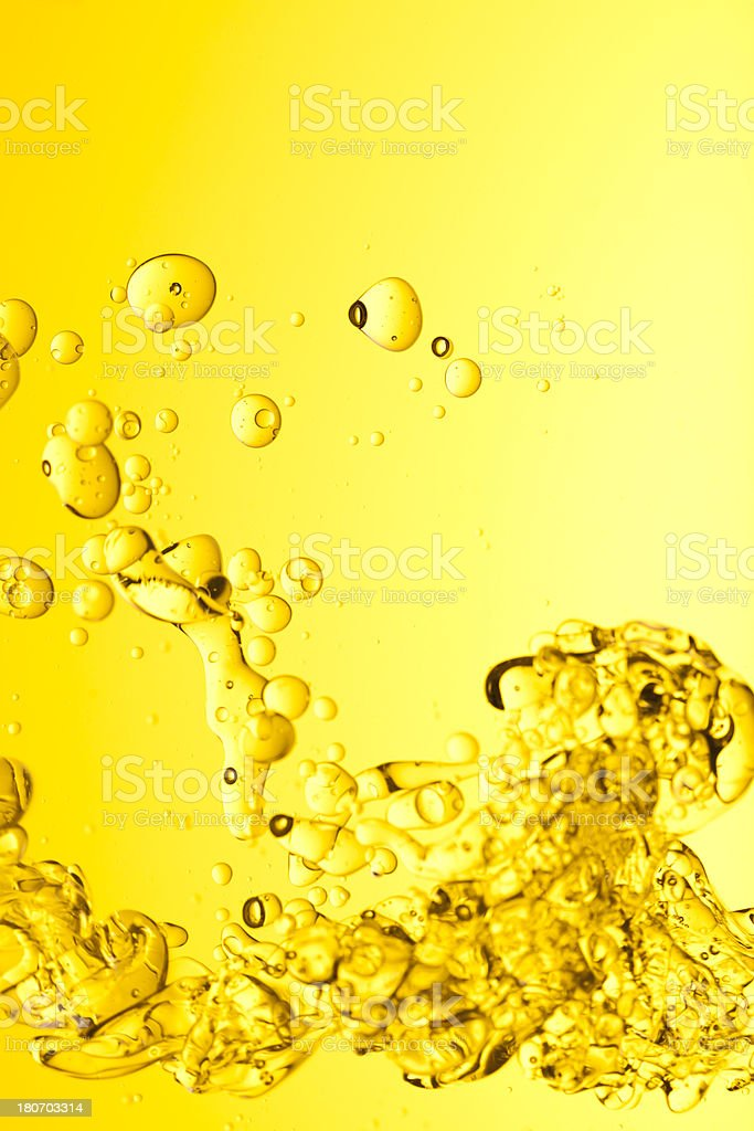 Yellow oil splashing into water background royalty-free stock photo