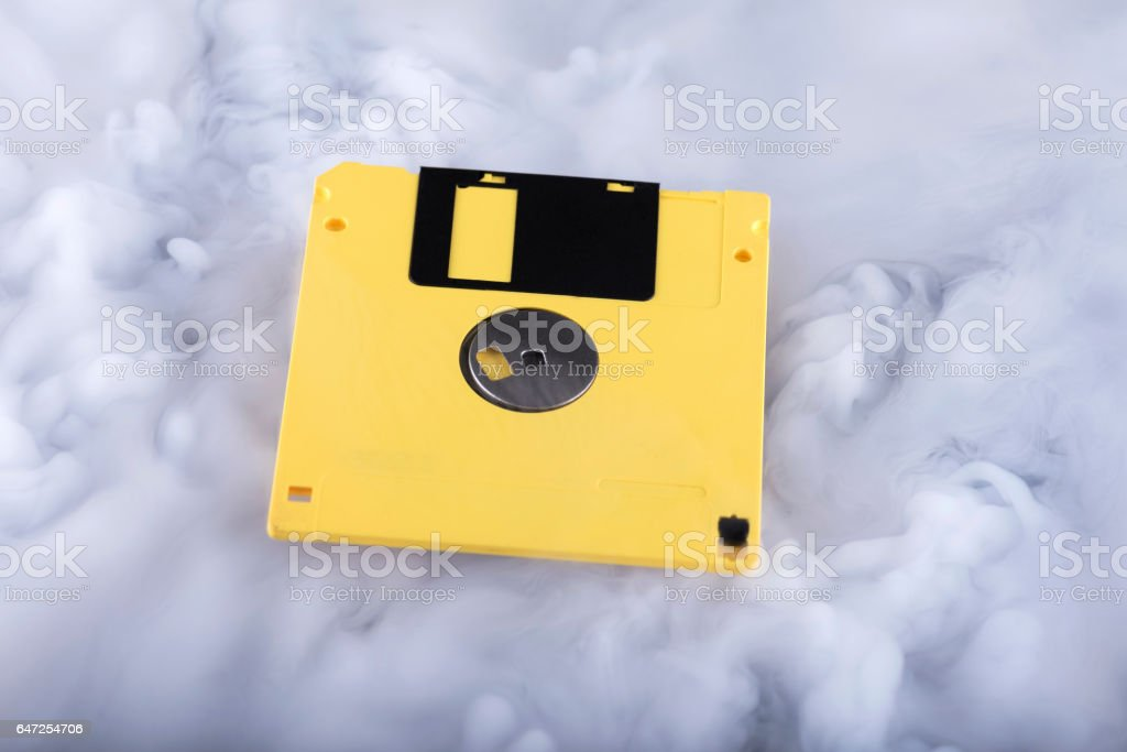 Yellow old and retro floppy disk. Information cloud conceptual image stock photo