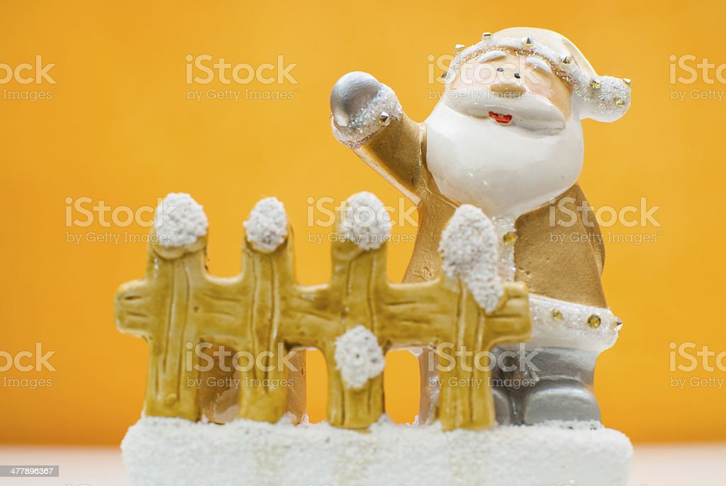 Yellow old time Santa Claus figurine on orange background stock photo
