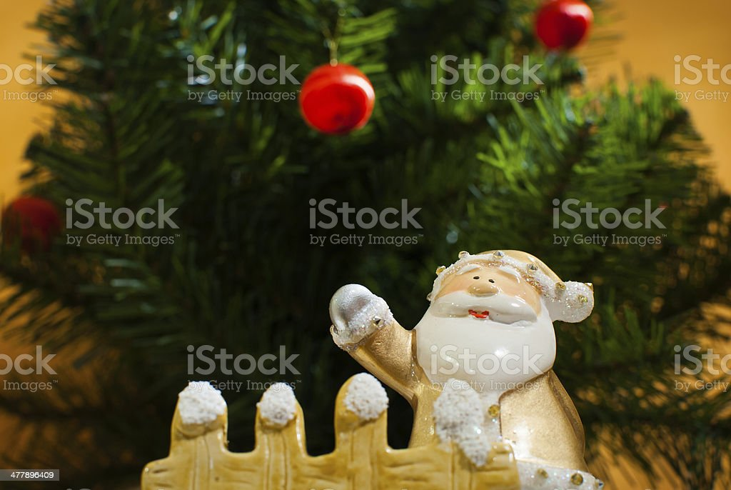 Yellow old time Santa Claus figurine standing behind garden fence stock photo