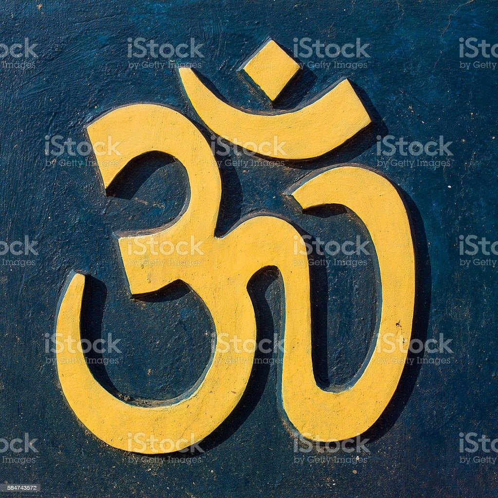Yellow Om/Aum symbol on dark blue wall stock photo