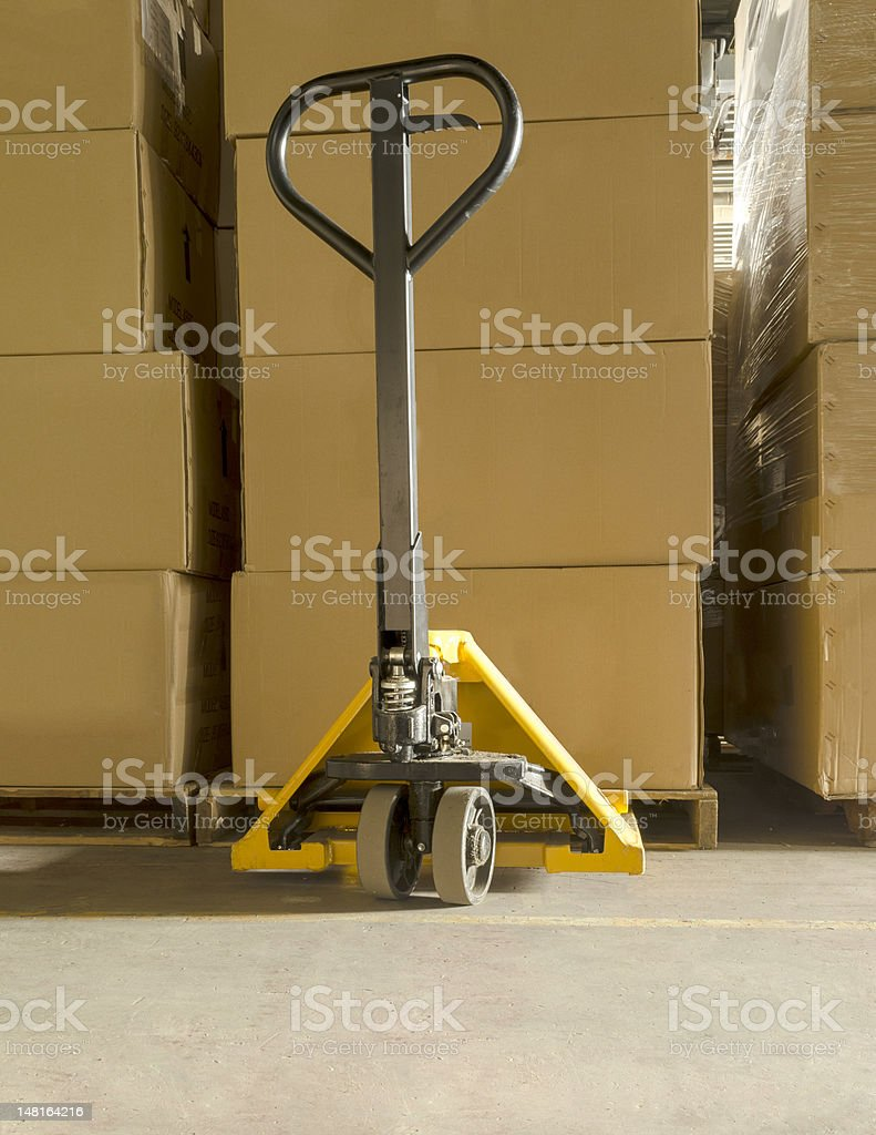 Yellow Pallet Jack with Brown Boxes stock photo