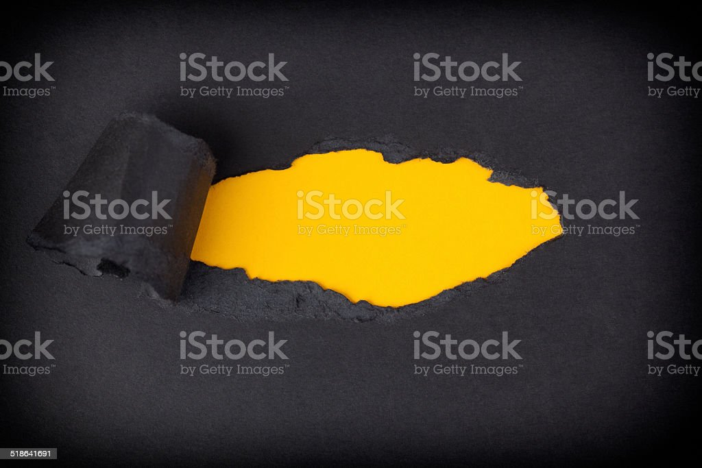Yellow paper background appearing behind torn black paper stock photo
