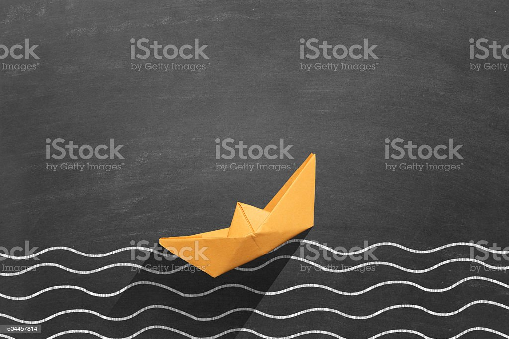 Yellow paper boat floating on water stock photo