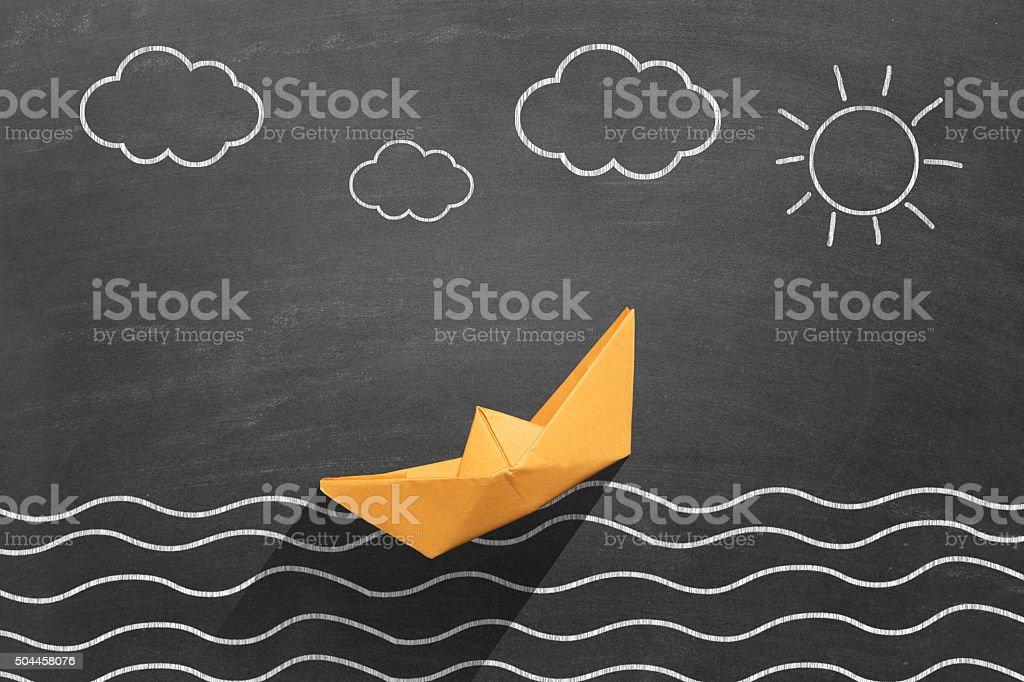 This drawing describing sea scene on blackboard. Yellow paper boat is...