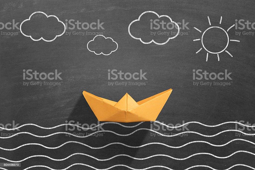 This drawing describing sea scene on blackboard. Yellow paper boat...